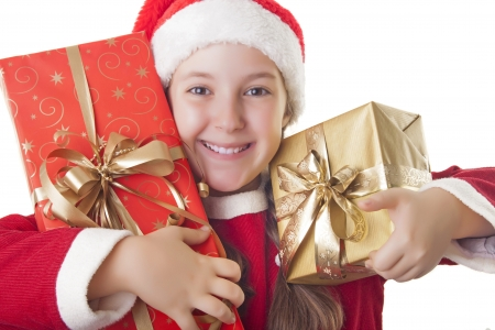 hat new year s eve: Beautiful girl dressed in Christmas clothes and red santa hat rejoicing with presents in her hands isolated on white background Stock Photo
