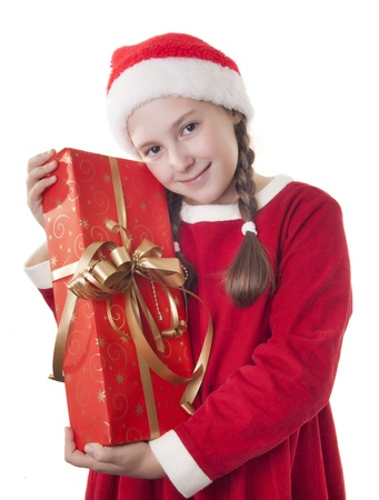 Beautiful girl dressed in Christmas clothes and red santa hat hugging present in her hands isolated on white background photo