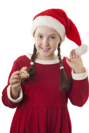 hat new year s eve: Beautiful girl dressed in Christmas clothes and red santa hat with cookie in her hands isolated on white background Stock Photo