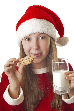 Beautiful girl dressed in Christmas clothes and red santa hat with cookie and milk in her hands isolated on white background photo