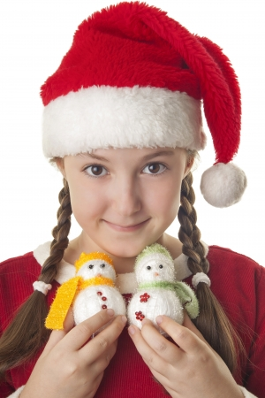 hat new year s eve: Beautiful girl dressed in Christmas clothes and red santa hat with two cute little snowmen in her hands isolated on white background