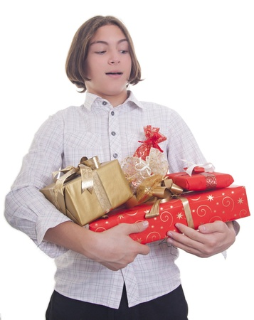 Handsome teenage boy with bunch of presents in his hands photo