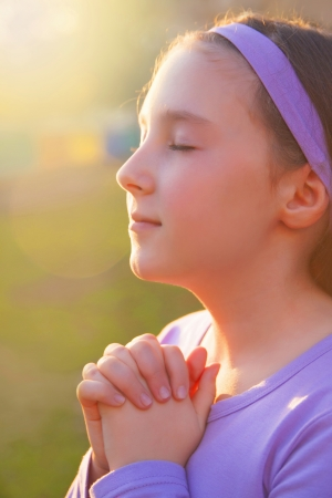 Girl praying with eyes closed et the sunset photo