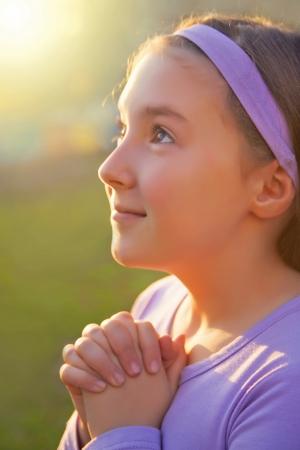 niño orando: Chica rezando con los ojos abiertos