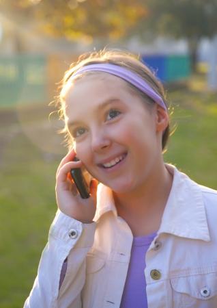 sholders: Girl Speaking On Cell Phone At Sunset Stock Photo