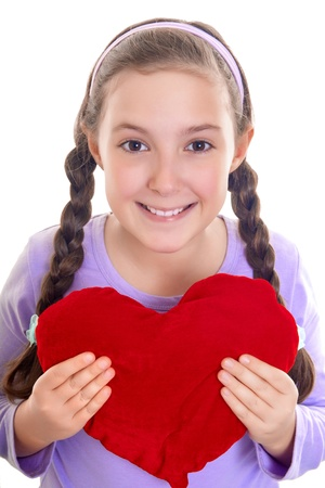 sholders: Little giirl holding a heart shaped pillow in her arms