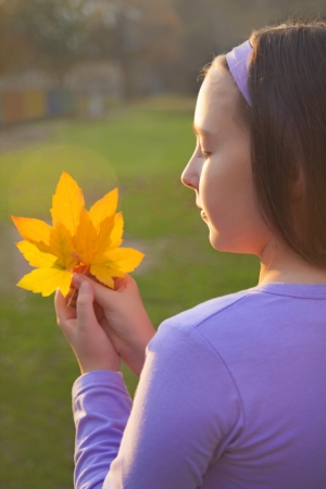sholders: Girl with yellow leafs in her hands at sunset