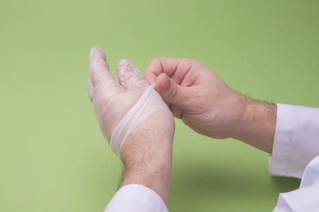 latex: Doctor Taking Off Latex Surgical Gloves