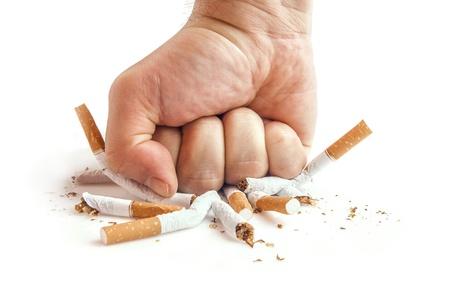 fumando: Puño humano rompiendo cigarrillos concepto contra el tabaquismo Foto de archivo