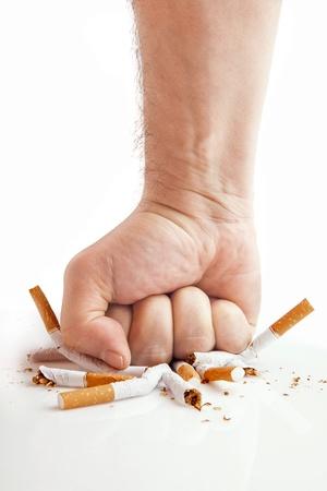 anti smoking: Human fist breaking cigarettes Anti smoking concept Stock Photo