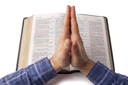 mains pri�re: Prier les mains sur la Bible ouverte isol� sur blanc