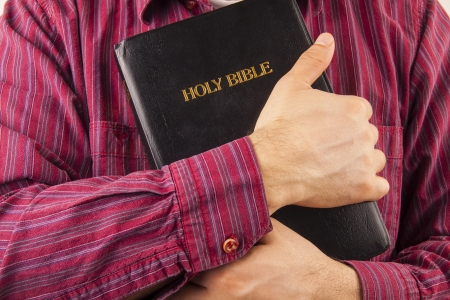 holy bible: Man in a red shirt hugging the Holy Bible