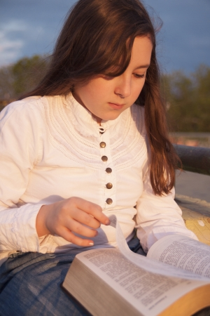Beautiful girl reading holy bible on a sun set photo