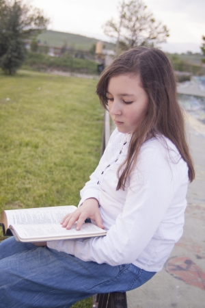 Beautiful girl reading a book in a park photo