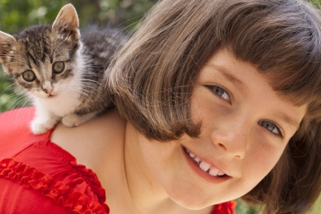 Little girl with cute kitten. Outdoor photo