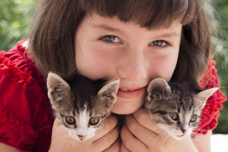 Little girl holding two cute kitten. Outdoor photo