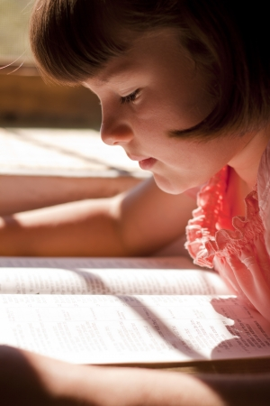 Beautiful Girl Reading Holy Bible. Sitting on a table photo