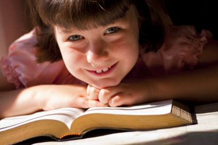 holy bible: Beautiful Girl Reading Holy Bible. Sitting on a table