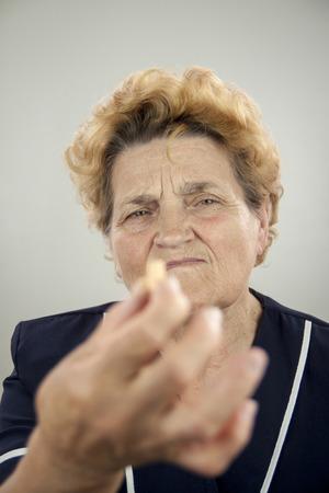 rheumatoid: Senior woman with Rheumatoid Arthritis. Holding pill