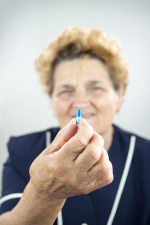 rheumatoid: Senior woman with rheumatoid arthritis holding pill Stock Photo