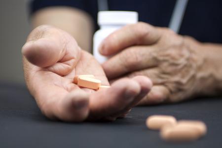 Hands Of Woman Deformed From Rheumatoid Arthritis holding pills photo