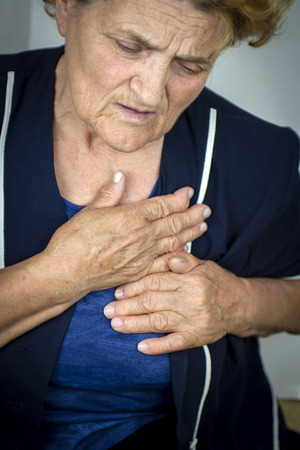 Senior woman having chest pain photo