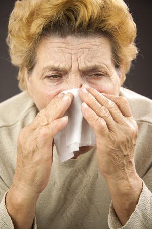 Senior woman sneezing. Using napkin photo