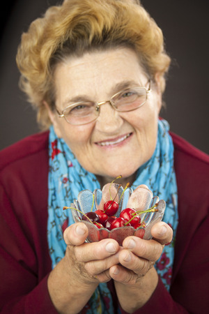 greeneyes: Senior woman holding cherries. Portrait