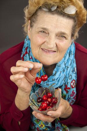 greeneyes: Senior woman holding cherries. Portrait