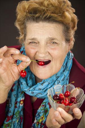 greeneyes: Senior woman eating cherries. Portrait Stock Photo