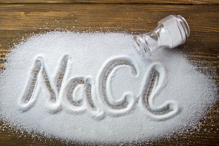 NaCl written on a heap of salt - Sodium Chloride Stock Photo