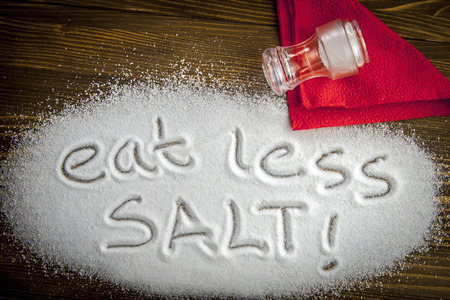 salt shaker: Eat less salt written on a heap of salt - antihypertensive campaign