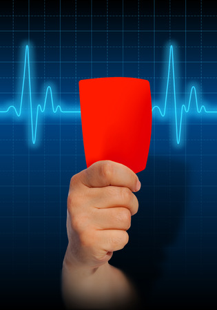 stress test: Hand holding red card on heart rate monitor expressing warning on heart condition, health hazard Stock Photo