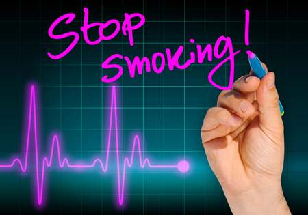 Hand writing message STOP SMOKING with heart rate monitor in the background expressing health hazard - Anti smoking campaign photo