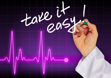 take it easy: Doctor hand writing message TAKE IT EASY! with heart rate monitor in the background