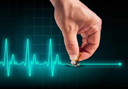 Hand putting out cigarette on heart beat line turquoise background - Anti smoking concept - Health hazard photo