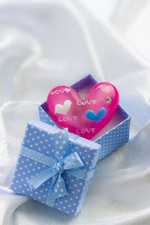 pink heart: Blue presents box with little pink heart of glass. For male
