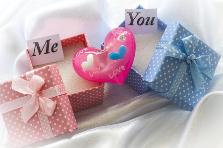 Two present boxes with pink heart. For female and male photo