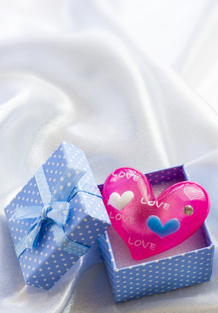Blue present box with little pink heart of glass. For male photo
