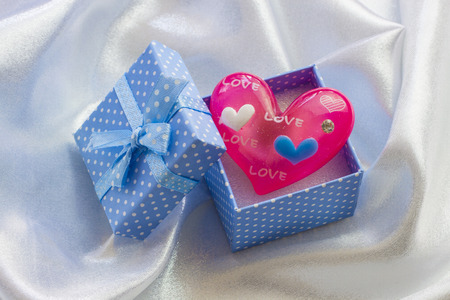 corazon rosa: Caja azul presente con poco coraz�n rosa de cristal. Para masculina Foto de archivo