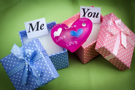 Presents boxes for female and male. Love messages. Green background photo
