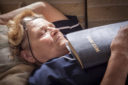 Adult woman fell asleep with a bible in her hands photo