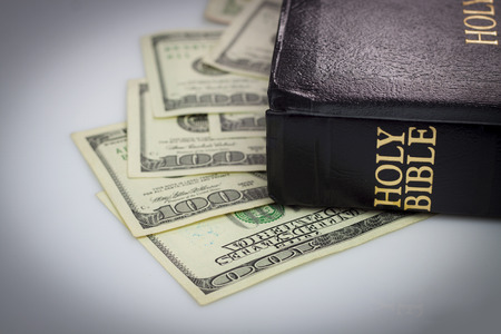 Holy Bible and money. Hundred dollars