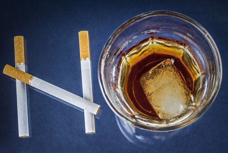 Cigarettes and glass of alcohol forming the word NO on blue background - Health concept - Anti smoking and anti alcoholism campaign