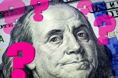 Benjamin Franklins portrait and question marks expressing financial uncertainty - Financial concept photo