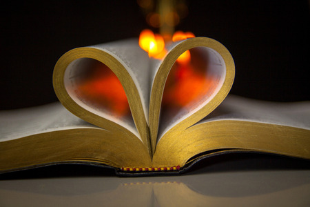 Holy Biible and Candles in the Background. Heart shape bible
