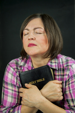 Adult woman praying on dark background photo