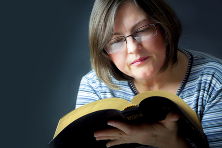 Adult Woman Reading a Bible. Close Standard-Bild