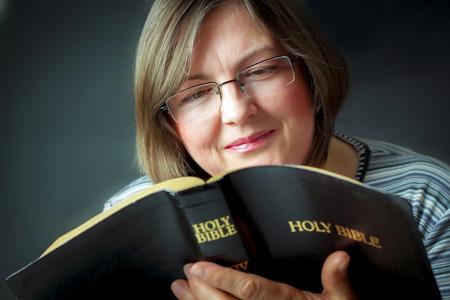 persona leyendo: Mujer adulta que lee una biblia. Cerca Foto de archivo