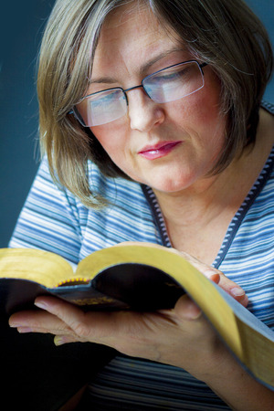 young woman reading bible: Adult Woman Reading a Bible. Close Stock Photo
